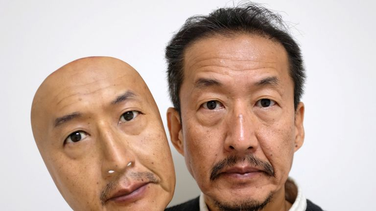 The president of Japan's REAL-f Co. shows off a hyper-realistic mask