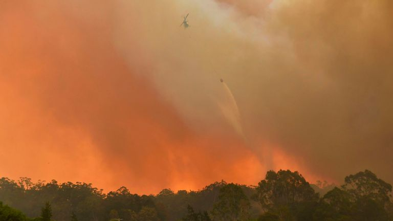 A helicopter drops water on a homestead as bushfires impact on farmland near the small town of Nana Glen, some 600kms north of Sydney on November 12, 2019