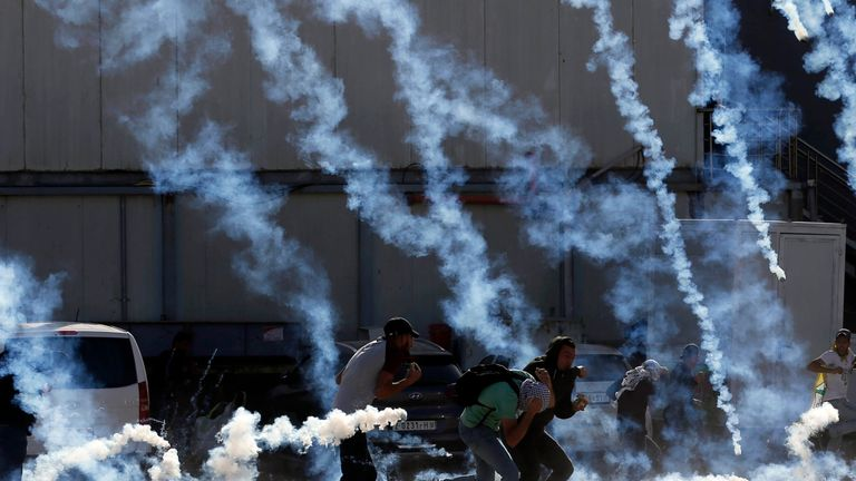 Palestinian youths run from tear gas smoke fired by Israeli security forces