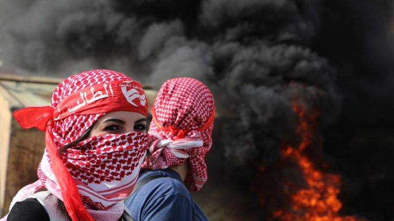 Masked Palestinian protesters stand amid clashes with Israeli forces at the entrance of the West Bank