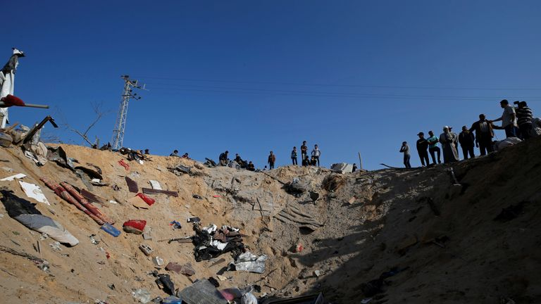 Palestinians gather at the scene of an Israeli air strike in the central Gaza Strip