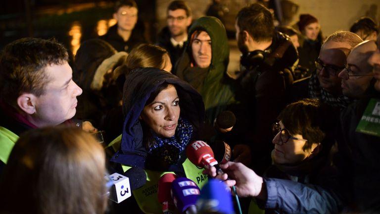 Paris mayor Anne Hidalgo talks to reporters as migrants are evacuated