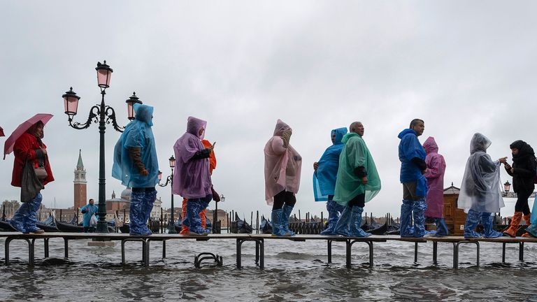 Tourists walk in high water Piazza San Marco in Piazza San Marco on November 12, 2019 in Venice, Italy