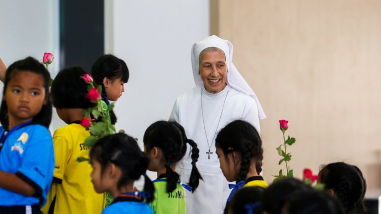 Sister Ana Rosa Sivori smiles as she walks with students at the St. Mary School in Udon Thani province