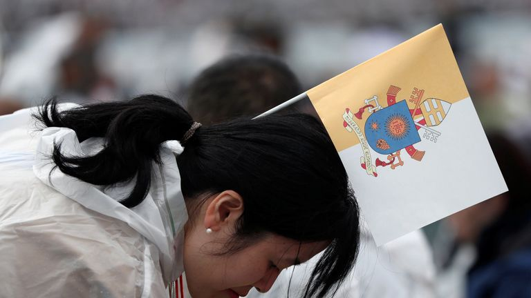 A wellwisher with a flag bearing the coat of arms of Pope Francis waits for his arrival for a Holy Mass in Nagasaki