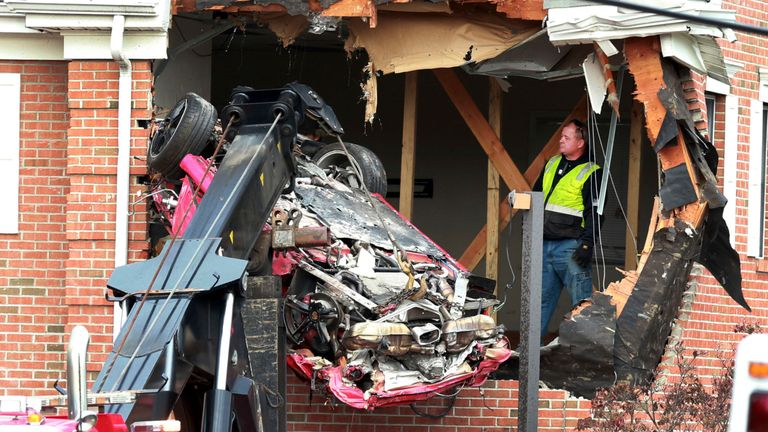 A Porsche is removed from the second story of a building after the convertible went airborne