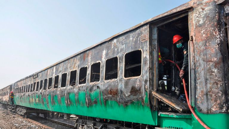 Firefighters work to cool down the burnt-out train carriages after a passenger train caught on fire near Rahim Yar Khan in Punjab province on October 31, 2019