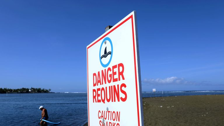 A man enters the water next to a sign warning on the danger of shark attacks at the L'Etang-Sale beach, on the Indian Ocean island of La Reunion on March 1, 2019