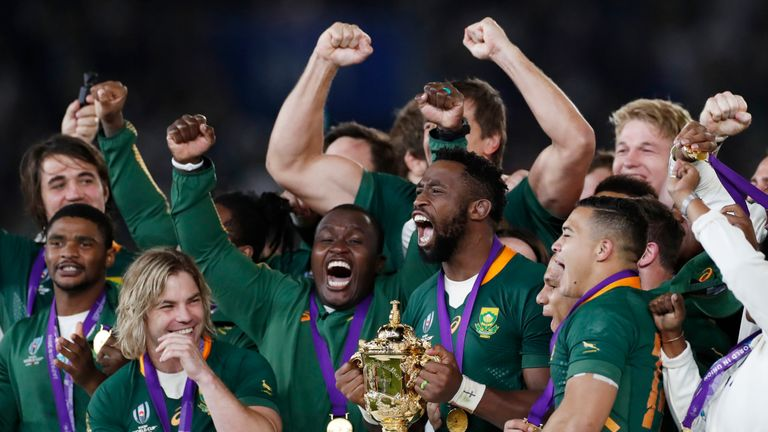 Springboks captain Siya Kolisi lifts the Webb Ellis Cup as his team celebrates winning the World Cup final
