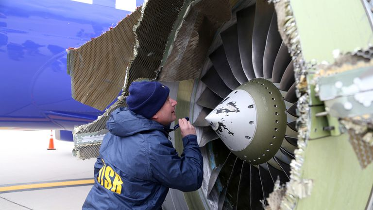 NTSB investigator Jean-pierre Scarfo examines damage to the CFM International 56-7B turbofan engine belonging Southwest Airlines Flight 1380 that separated during flight Philadelphia International Airport April 17, 2018 in Philadelphia, Pennsylvania. Investigators can't explain with certainty why the left engine in the Boeing 737 malfunctioned but are directing their attention to metal fatigue on fan blades