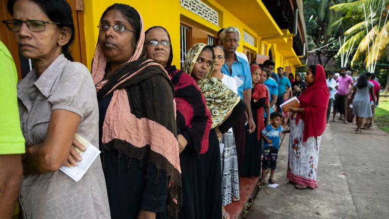 Sri Lankan people wait in line to vote on Saturday