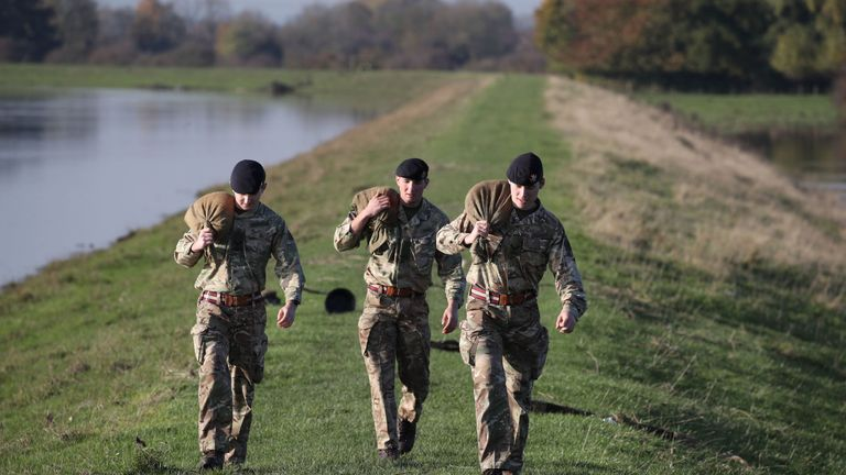British Army soldiers carry sandbags along an embankment at Stainforth, near Doncaster