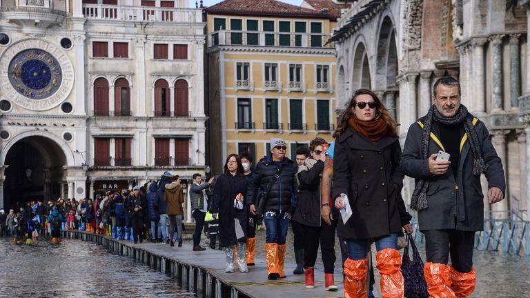 Tourists use a temporary platform to cross St Mark's Square