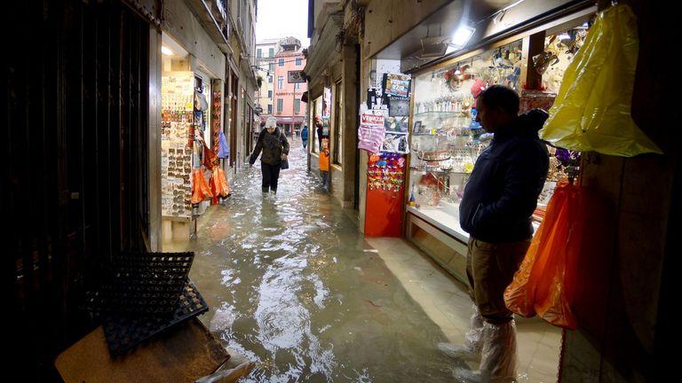 A man stands outside a souvenir shop as a woman walks across a flooded alleyway