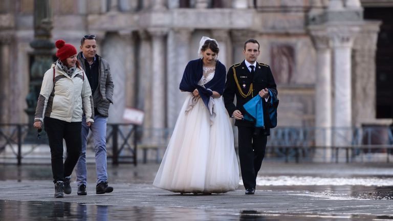 A newlywed couple walk across a flooded square in the lagoon city