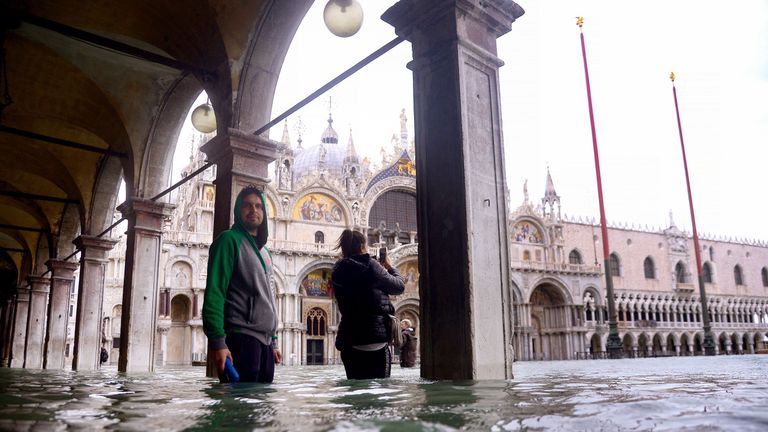 People take photos from a flooded arcade