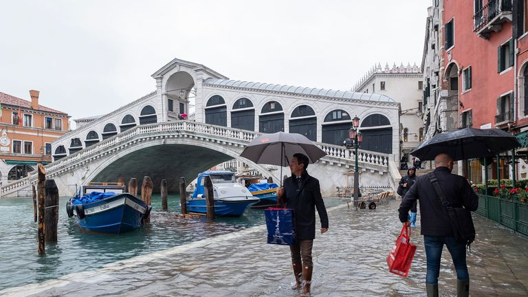Tourists walk in high water near Rialto bridge in Piazza San Marco on November 12, 2019 in Venice, Italy