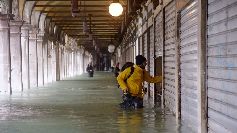 A man stands by a closed shop in a flooded arcade by St Mark's square