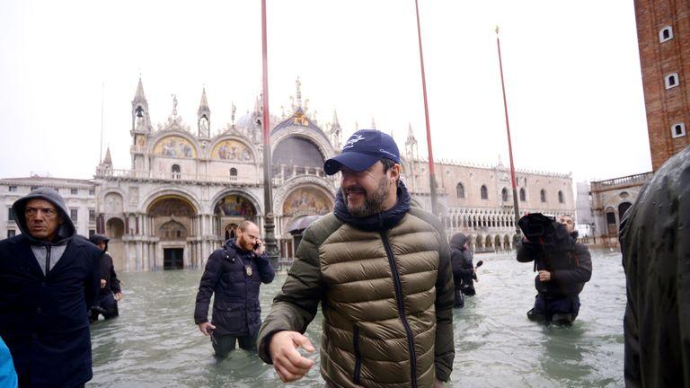 Head of Italy's far-right League (Lega) party, Matteo Salvini (C) walks across the flooded St. Mark's Square