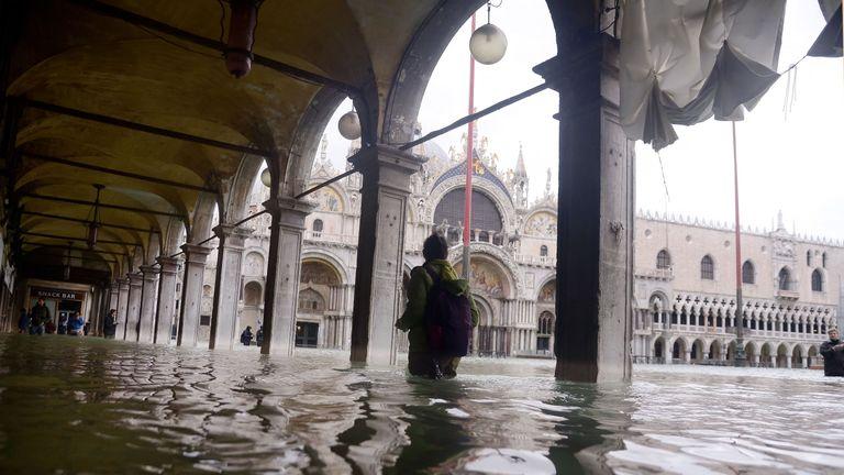 A person walks across a flooded arcade by St Mark's Basilica