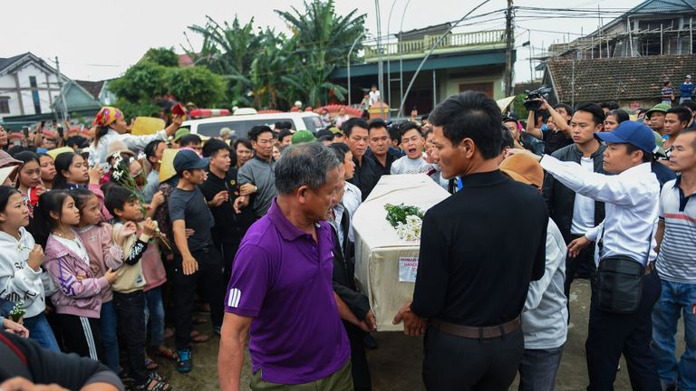 A crowd gathered as the casket with 33-year-old Nguyen Van Hung's body is carried by relatives in Nghe An province
