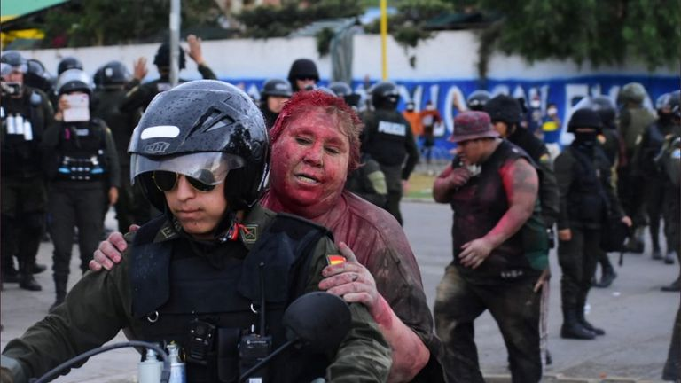Police rescue Vinto mayor Patricia Arce Guzman on a motorcycle after people threw paint and dirt on her following a fire in Vinto's Town Hall, Quillacollo, Bolivia, November 6, 2019. Pic: Daniel James, Los Tiempos Bolivia