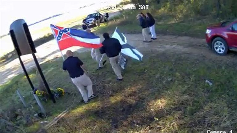 Men holding flags associated with white nationalist groups seen at the site