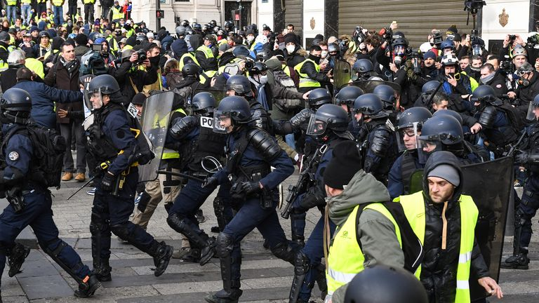 "PARIS, FRANCE - DECEMBER 08:  French police charge as demonstrators take part in the demonstration of the yellow vests near the Arc de Triomphe on December 8, 2018 in Paris France. ''Yellow Vests' (""Gilet Jaunes"" or ""Vestes Jaunes"") is a protest movement without political affiliation which was inspired by opposition to a new fuel tax. After a month of protests, which have wrecked parts of Paris and other French cities, there are fears the movement has been infiltrated by ""ultra-violent"" protesters. Today's protest has involved at least 5,000 demonstrators gathering in the Parisian city centre with police having made over 200 arrests so far.  (Photo by Jeff J Mitchell/Getty Images)"