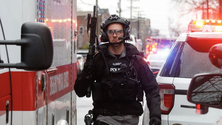 Police officers arrive to the scene where active shooting is happening in Jersey City on December 10, 2019. - One officer was shot when two gunmen with a long rifle opened fire in Jersey City, New Jersey, on the afternoon of December 10, 2019 , according to two officials. Two suspects were barricaded in a convenience store, the officials said. One officer was being taken to a nearby hospital. (Photo by Kena Betancur / AFP) (Photo by KENA BETANCUR/Afp/AFP via Getty Images)