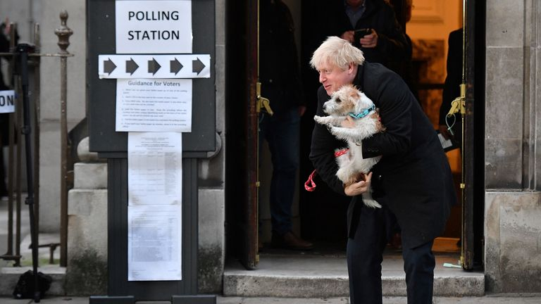 Britain's Prime Minister Boris Johnson poses with his dog Dilyn as he leaves from a Polling Station, after casting his ballot paper and voting, in central London on December 12, 2019, as Britain holds a general election. (Photo by DANIEL LEAL-OLIVAS / AFP) (Photo by DANIEL LEAL-OLIVAS/AFP via Getty Images)