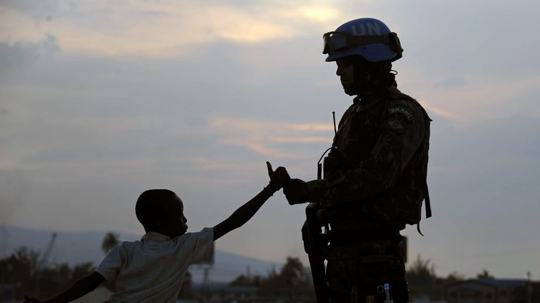 A Brazilian soldier with the MINUSTAH force greets a boy at a shantytown in Port-au-Prince on March 2, 2013. Brazil began the process of reducing its peace-keeping forces operating under the MINUSTAH mandate from 1910 to 1450 men, the same number that was there before the deadly 2010 earthquake that left a death toll of more than 250,000.   AFP PHOTO/VANDERLEI ALMEIDA        (Photo credit should read VANDERLEI ALMEIDA/AFP via Getty Images)