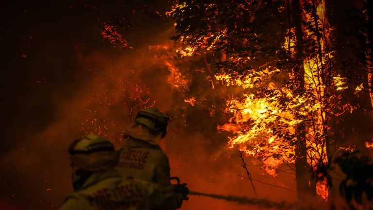 SYDNEY, AUSTRALIA - DECEMBER 19: Fire and Rescue personal use a hose as they try to extinguish a bushfire as it burns near homes on the outskirts of the town of Bilpin on December 19, 2019 in Sydney, Australia. (Photo by David Gray/Getty Images)