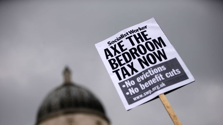 "LONDON, ENGLAND - MARCH 30:  A protestor holds a sign while demonstrating against the proposed ""bedroom tax"" gather in Trafalgar Square before marching to Downing Street on March 30, 2013 in London, England. Welfare groups are protesting the government's plans to cut benefits where families have surpassed the number of rooms they require. (Photo by Matthew Lloyd/Getty Images)"