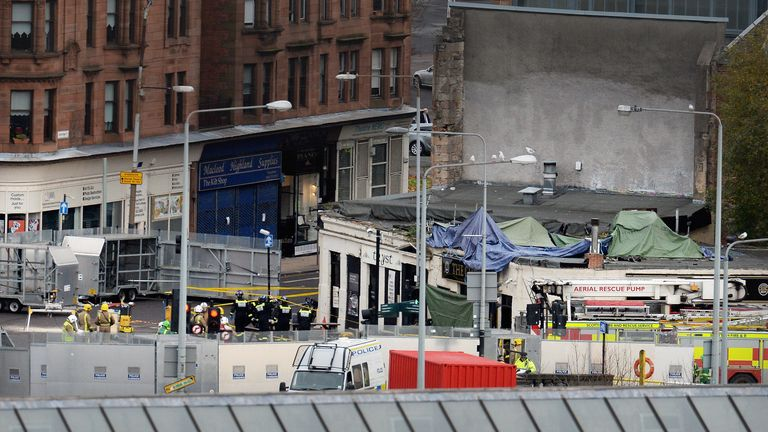 GLASGOW, SCOTLAND - NOVEMBER 30:  Rescue workers attend the scene at a pub on Stockwell Street where a police helicopter crashed on the banks of the River Clyde November 30, 2013 in Glasgow, Scotland, United Kingdom. Police Scotland have confirmed the crash at The Clutha bar which happened at 22:25 on Friday night, in which they have confirmed one death as a result so far.  (Photo by Jeff J Mitchell/Getty Images)