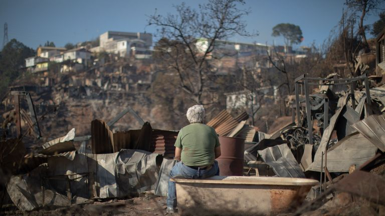 TOPSHOT - A man looks at the destruction caused by a forest fire at the Rocuant hill in Valparaiso, Chile, on December 25, 2019. - More than 100 houses were affected by a forest fire Tuesday in Valparaiso, where a red alert was declared. (Photo by Pablo Rojas Maradiaga / AFP) (Photo by PABLO ROJAS MARADIAGA/AFP via Getty Images)
