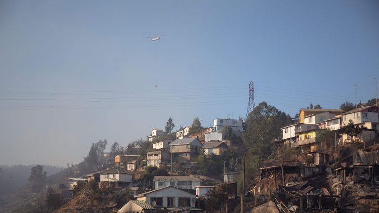 A helicopter transports water to extinguish a forest fire near the Rocuant hill in Valparaiso, Chile, on December 25, 2019. - More than 100 houses were affected by a forest fire Tuesday in Valparaiso, where a red alert was declared. (Photo by Pablo Rojas Maradiaga / AFP) (Photo by PABLO ROJAS MARADIAGA/AFP via Getty Images)