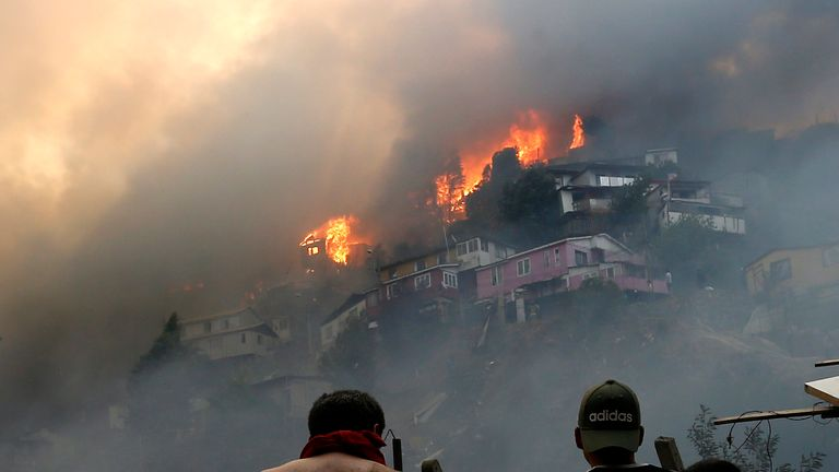 "Men look at houses burning during a forest fire at the Rocuant hill in Valparaiso, Chile, on December 24, 2019. - Some 50 houses were affected by a forest fire Tuesday in Valparaiso, where a red alert was declared. (Photo by RAUL ZAMORA / ATON CHILE / AFP) / Chile OUT / RESTRICTED TO EDITORIAL USE - MANDATORY CREDIT ""AFP PHOTO / ATON / RAUL ZAMORA "" - NO MARKETING NO ADVERTISING CAMPAIGNS - DISTRIBUTED AS A SERVICE TO CLIENTS-CHILE OUT (Photo by RAUL ZAMORA/ATON CHILE/AFP via Getty Images)"