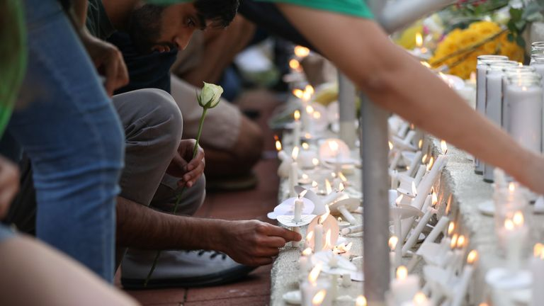 TOPSHOT - Students lay candles and flowers at the steps of Kennedy Hall to honor the victims of a shooting the day earlier on the University of North Carolina, Charlotte, North Carolina on May 1, 2019. - A 21-year-old student gave his life to save others by tackling a gunman who was shooting up a university classroom, police in the US said May 1, 2019.  Charlotte-Mecklenburg Police Chief Kerr Putney said the authorities were still trying to find a motive for Tuesday's attack at the University of North Carolina, which left undergraduate Riley Howell and another student dead. (Photo by Logan Cyrus / AFP)        (Photo credit should read LOGAN CYRUS/AFP via Getty Images)