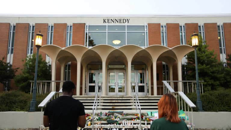 TOPSHOT - Students lay candles and flowers at the steps of Kennedy Hall to honor the victims of a shooting the day earlier at the University of North Carolina Charlotte, in Charlotte, North Carolina on May 1, 2019. - A 21-year-old student gave his life to save others by tackling a gunman who was shooting up a university classroom, police in the US said May 1, 2019.  Charlotte-Mecklenburg Police Chief Kerr Putney said the authorities were still trying to find a motive for Tuesday's attack at the University of North Carolina, which left undergraduate Riley Howell and another student dead. (Photo by Logan Cyrus / AFP)        (Photo credit should read LOGAN CYRUS/AFP via Getty Images)