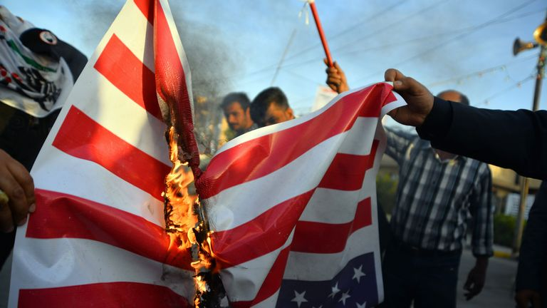 Iraqis burn a US national flag on December 30, 2019, during a demonstration to denounce the previous night's attacks by US planes on several bases belonging to the Hezbollah brigades near Al-Qaim, an Iraqi district bordering Syria. - US air strikes against a pro-Iran group in Iraq reportedly killed at least 25 fighters, triggering anger in a country caught up in mounting tensions between Tehran and Washington. (Photo by Haidar HAMDANI / AFP) (Photo by HAIDAR HAMDANI/AFP via Getty Images)