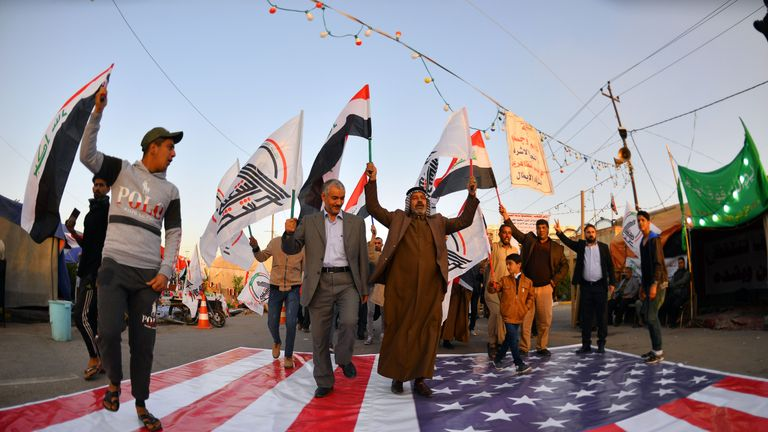 Iraqis walk on a US national flag on December 30, 2019, during a demonstration to denounce the previous night's attacks by US planes on several bases belonging to the Hezbollah brigades near Al-Qaim, an Iraqi district bordering Syria. - US air strikes against a pro-Iran group in Iraq reportedly killed at least 25 fighters, triggering anger in a country caught up in mounting tensions between Tehran and Washington. (Photo by Haidar HAMDANI / AFP) (Photo by HAIDAR HAMDANI/AFP via Getty Images)