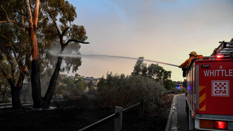 """A fire truck dampens down a fire after a bushfire encroached on the outer suburbs of Melbourne on December 30, 2019. - Hundreds of firefighters were removed from bushland deemed too dangerous as a heatwave swept Australia on December 30, with seven major blazes declared """"emergencies"""" in the country's south-east. (Photo by William WEST / AFP) (Photo by WILLIAM WEST/AFP via Getty Images)"""