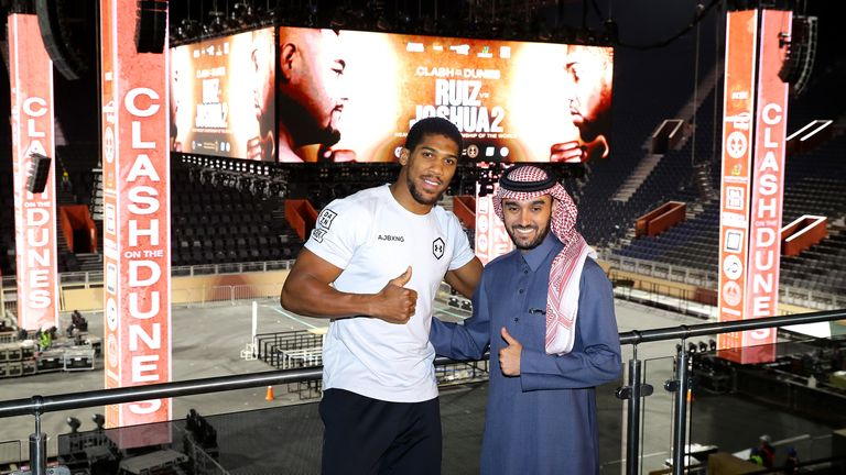 Anthony Joshua and Prince Abdulaziz pose in front of the stage