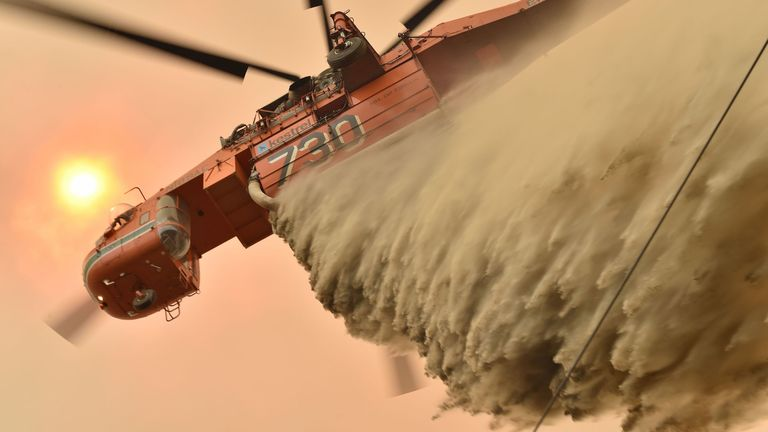 A helicopter drops fire retardant to protected a property in New South Wales
