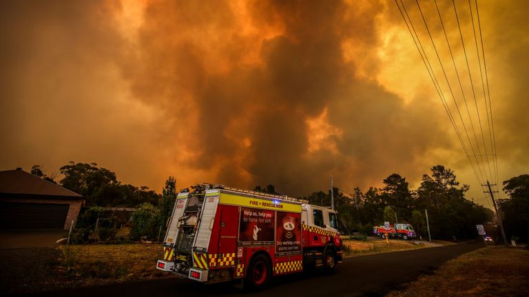 Firemen prepare as a bushfire approaches homes on the outskirts of the town of Bargo