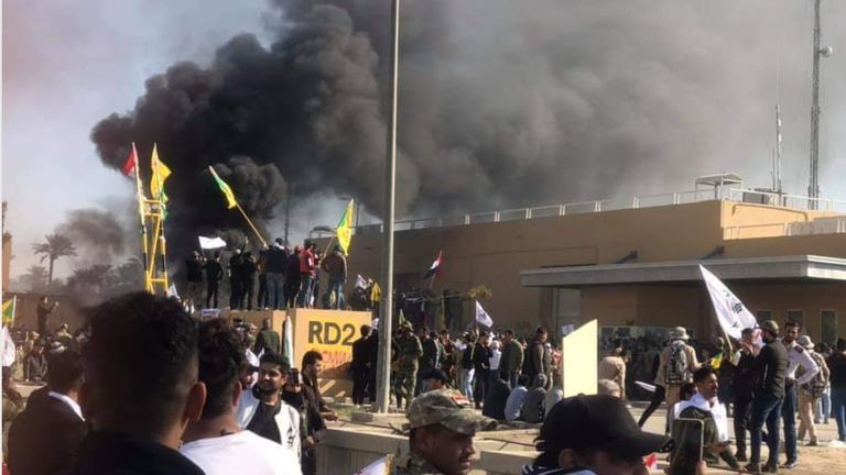 Smoke rises as crowds attempt to storm the US embassy in Baghdad