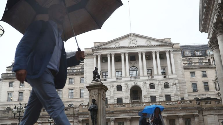 Pedestrians shelter under umbrellas in front of the Royal Exchange and the Bank of England, in London