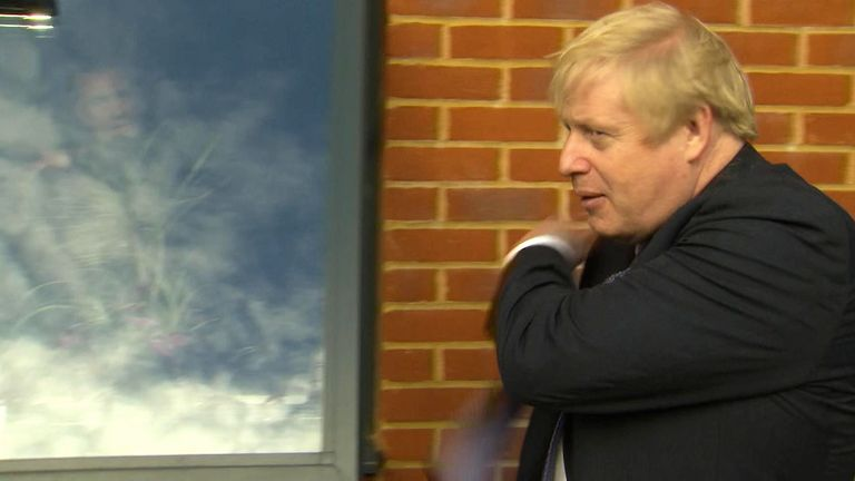 Boris Johnson brushes his jacket