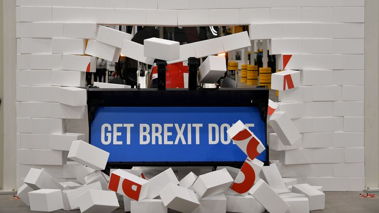 "Boris Johnson drives a Union flag-themed JCB, with the words ""Get Brexit Done"" inside the digger bucket, through a fake wall emblazoned with the word ""GRIDLOCK"""