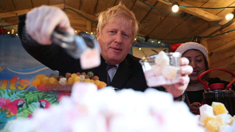 Boris Johnson gestures as he visits a Christmas market during a Conservative Party general election campaign event in Salisbury, southwest England on December 3, 2019